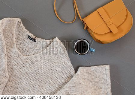 Clothes, A Cup Of Coffee, A Women's Bag Laid Out On A Gray Background Top View
