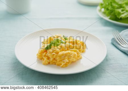 Scrambled Eggs, Omelette. Breakfast With Pan-fried Eggs. Texture Of Omelet On White Plate On Green M