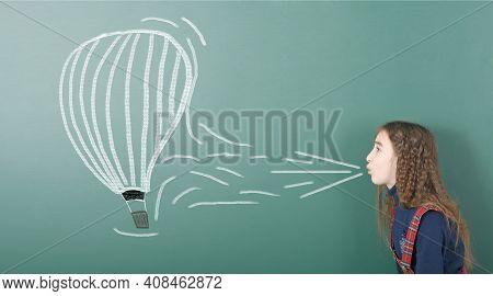 Pre-adolescent Girl Blowing On Painted Balloon Aeronautics. Portrait Photo On School Board Backgroun