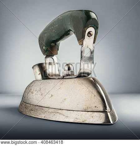 Old Iron. Electric Iron For Ironing On A Gray Background With Cold Toning. Old Household Appliances.