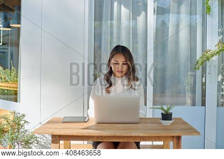 Professional Female Worker Uses Her Laptop Sitting At Table Outside In Background Of Modern Building