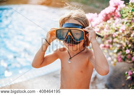 Portrait Of A Youth Boy With Naked Body And Holding His Eyewear He Poses In Background Of Swimming P