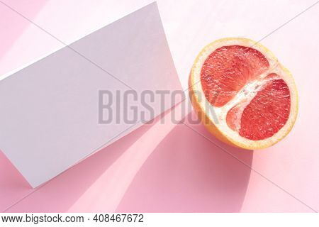 Summer Still Life With Half Of Grapefruit And Blank Paper Card.on Pink Background. Invitation Mockup