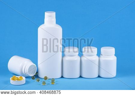 Five Pills Medicine Bottles On Blue Background With Copy Space For Text. Toppled Over Box And Spille