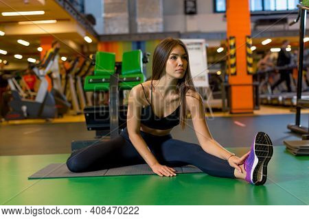 Sexy Young Girl In Sportswear Sits On The Gym Mat Doing Stretching In The Gym And Looking Ahead. Pho
