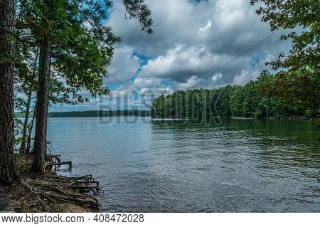 View Of Lake Lanier, Georgia From The Shoreline With Trees Alongside With Exposed Roots And The Boat