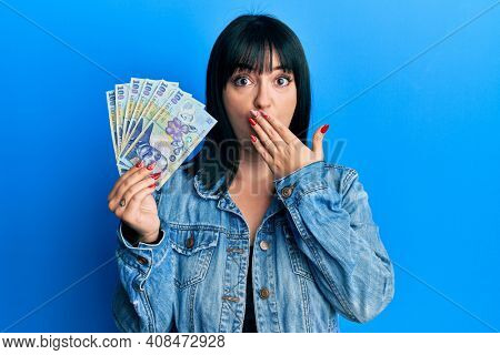 Young hispanic woman holding 100 romanian leu banknotes covering mouth with hand, shocked and afraid for mistake. surprised expression