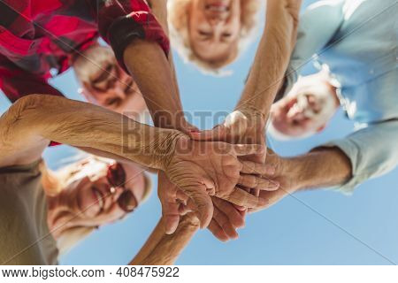 Low Angle View Of Group Of Cheerful Active Senior People Enjoying Sunny Summer Day Outdoors, Gathere