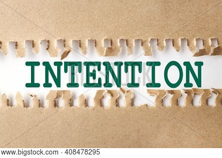 Intention. Text On White Paper Over Torn Paper Background.
