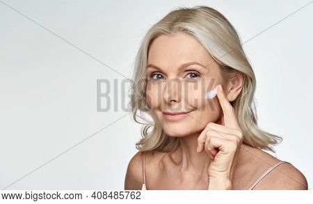 Smiling 50s Middle Aged Mature Older Woman Applying Facial Cream On Face Looking At Camera Isolated
