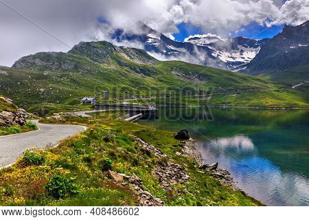 View of road along green shores and small alpine lake as mountains on background in Piedmont, Northern Italy.