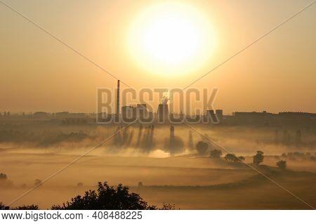 Plant At Dawn, Factory With Smokestacks At Dawn Near The Lakes