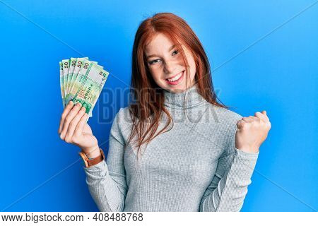 Young red head girl holding 50 hong kong dollars banknotes screaming proud, celebrating victory and success very excited with raised arm