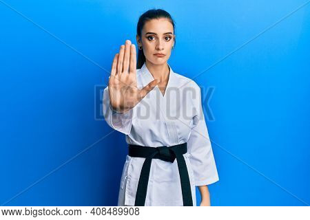 Beautiful brunette young woman wearing karate fighter uniform with black belt doing stop sing with palm of the hand. warning expression with negative and serious gesture on the face.