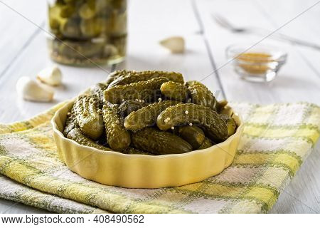 Delicious Pickled Cornichons In A Yellow Ceramic Bowl Over Checkered Napkin On A Table. Whole Green