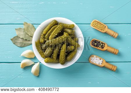 Crunchy Pickled Cornichons In A White Ceramic Bowl, Garlic, Bay Leaves, Salt, Pepper And Mustard See
