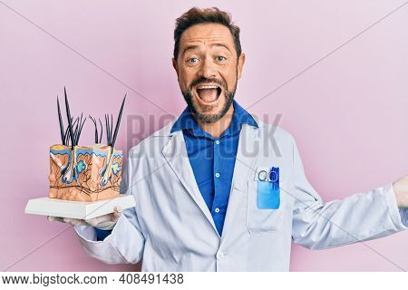 Middle age doctor man holding model of human anatomical skin and hair celebrating achievement with happy smile and winner expression with raised hand
