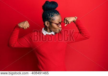 Young african american woman wearing casual clothes and glasses showing arms muscles smiling proud. fitness concept.