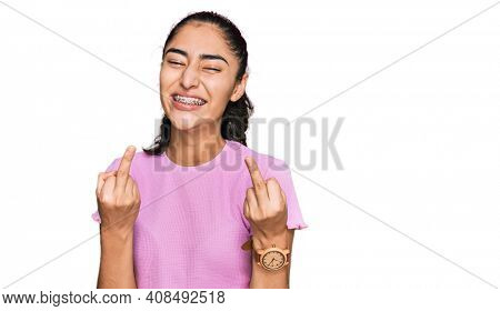 Hispanic teenager girl with dental braces wearing casual clothes showing middle finger doing fuck you bad expression, provocation and rude attitude. screaming excited