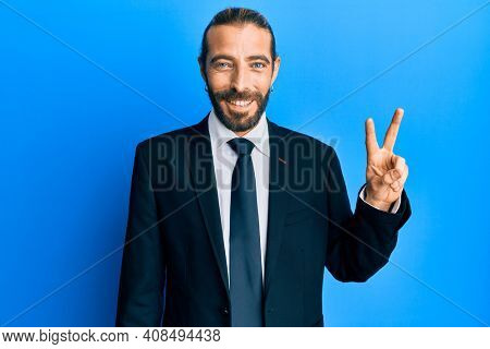 Attractive man with long hair and beard wearing business suit and tie smiling with happy face winking at the camera doing victory sign. number two.