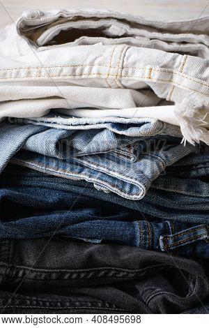 Stack Of Jeans. Denim Jeans Texture Or Denim Jeans Background, Close-up. Vertical.