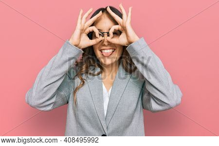 Young brunette woman wearing business clothes doing ok gesture like binoculars sticking tongue out, eyes looking through fingers. crazy expression.