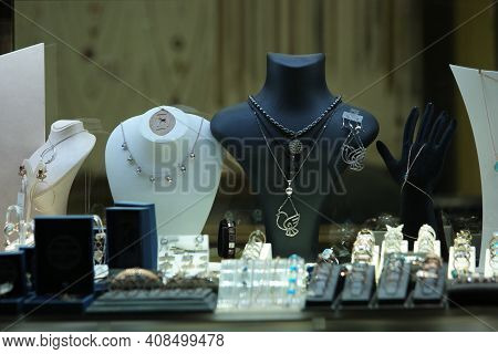 Female Jewelry At Shop Window. Showcase With Jewelry On Black Mannequins.