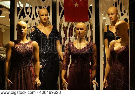 Female Mannequins Dressed In Beautiful Evening Dresses. Close Up Of Five Long Evening Dresses On Man