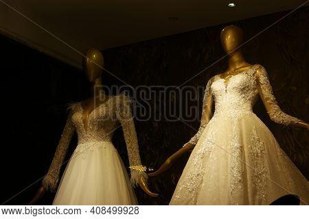 Stylish Wedding Dresses On Mannequins. Mannequins In Luxury Wedding Dresses, Dark Background. Weddin