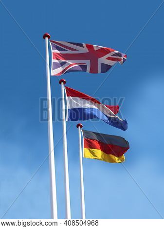 Flags Of United Kingdom, France And Germanyon Flagpoles. Flag Of United Kingdom Is On Top. Blue Sky