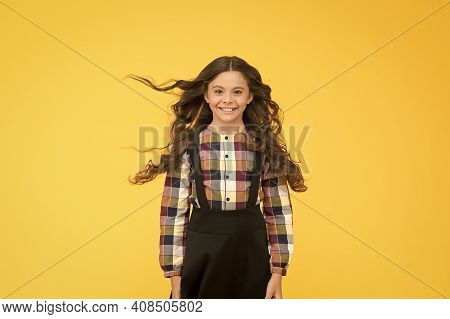 Salon Interested In My Hair. Happy Child With Long Hair Yellow Background. Small Girl With Wavy Brun