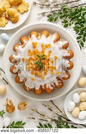 Easter Yeast Cake Babka Covered With Icing With Candied Orange Peel On A White Plate Top View. A Tra