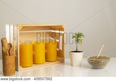 Three Jars Of Cbd Honey Placed In A Wooden Crate. Around The Crate Are Positioned A Marijuana Plant