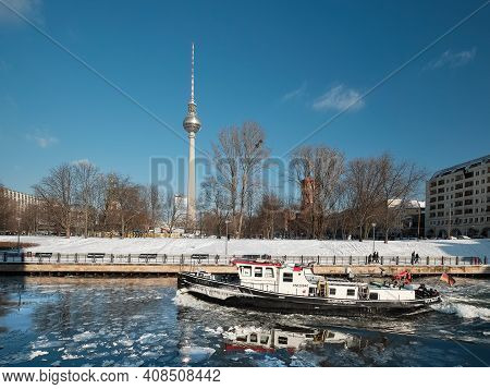 Berlin Riverside Under Snow. Boat Crashes Ice On Spree River. Panoramic Winter View With City Skylin