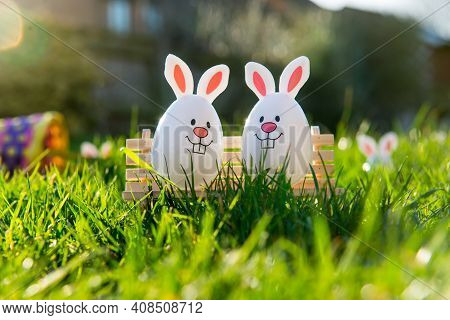 Creative Easter Composition Of Funny Easter Eggs With Bunny Ears Sitting On Bench On Green Grass Bac