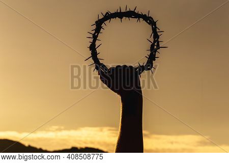 Silhouette Of Hands Holding Crown Of Christ In Golden Sky, Concept Of Divine Salvation, Catholic Pra
