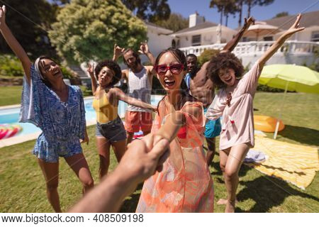 Diverse group of happy friends having fun dancing at a pool party. hanging out, and posing for the camera outdoors in summer.