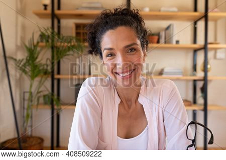 Portrait of smiling caucasian woman sitting at desk, working from home. Staying at home in self isolation during quarantine lockdown.