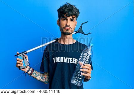 Young hispanic man holding plastic bottle and litter picker to recycle depressed and worry for distress, crying angry and afraid. sad expression.