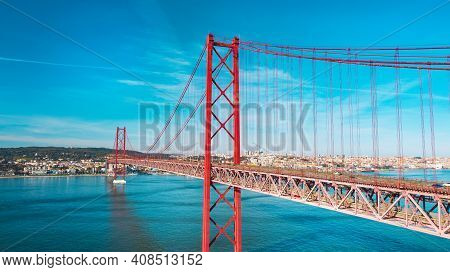 Aerial View Or Drone Photo Of The 25 De April Bridge. Red Bridge Is Connecting Lisbon And Almada Acr