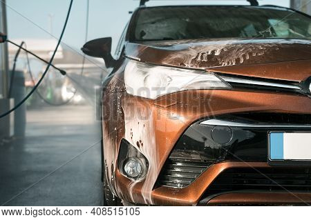 Washing Automobile In Self Serve Car Wash. Cleaning Car Using High Pressure Water At Car Washing Sta