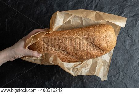 Woman Unwrapping With Her Hands Breads Paper On Black Background