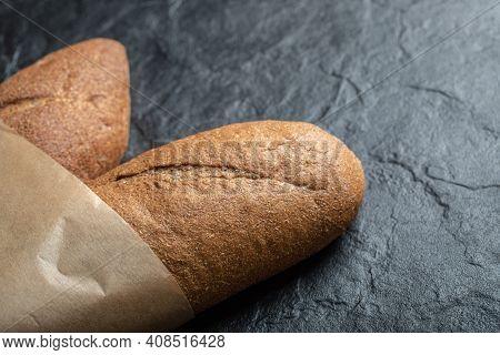 Freshly Baked British Baton Loaf Breads In Paper Bag