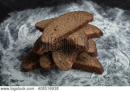 Freshly Baked Brown Bread Slices On White Flour Background