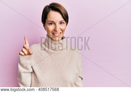 Young brunette woman with short hair wearing casual winter sweater showing and pointing up with finger number one while smiling confident and happy.