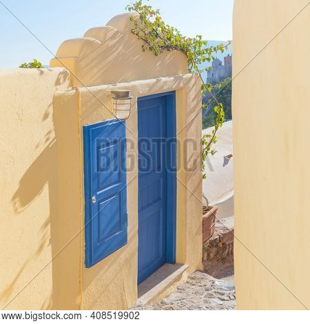 Old blue door and window in the narrow street. Conceptual Artistic Fragments of traditional buildings in Oia on Santorini. A picturesque view of the Santorini cycladic houses on a small street . Oia