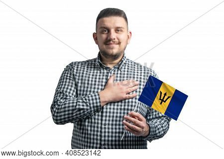 White Guy Holding A Flag Of Barbados And Holds His Hand On His Heart Isolated On A White Background