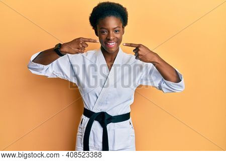 Young african american girl wearing karate kimono and black belt smiling cheerful showing and pointing with fingers teeth and mouth. dental health concept.