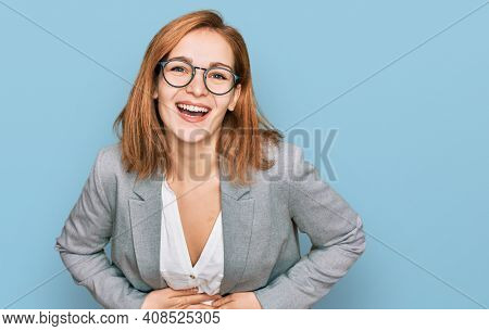 Young caucasian woman wearing business style and glasses smiling and laughing hard out loud because funny crazy joke with hands on body.