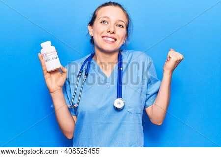 Young beautiful blonde woman wearing doctor uniform holding pills screaming proud, celebrating victory and success very excited with raised arm